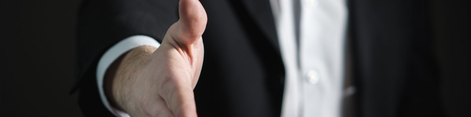 Man in busines suit reaches out to shake hand